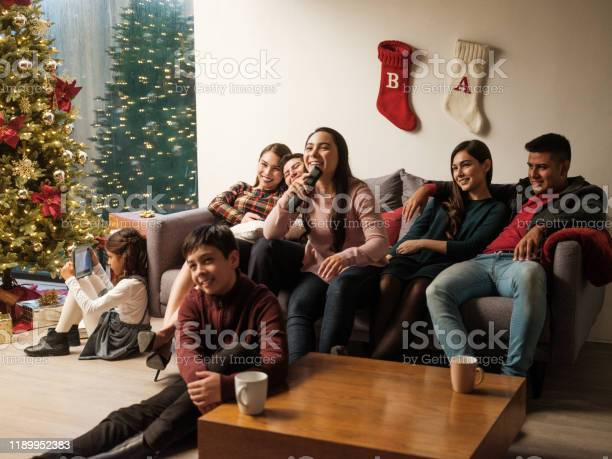 Young Latin People Sitting On Sofa At Home During Christmas Stock Photo - Download Image Now
