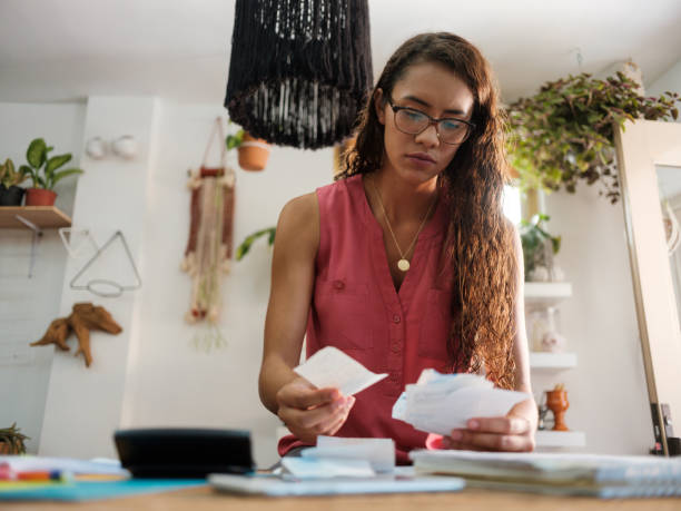 Young latin woman holding receipts and looking at them. stock photo