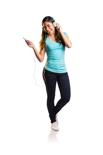A young latin woman listening to music with headphones and smiling away in a vertical full length shot with white background.