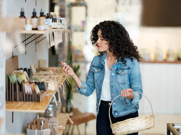 Young latin woman looking at products and holding shopping basket stock photo