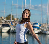 young latin woman on harbor with sailing ships in background laughing happy
