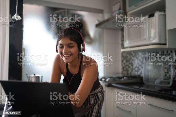 Young latin woman using laptop while listening to music at home picture id1132149387?b=1&k=6&m=1132149387&s=612x612&h=brbl7owpfkmj8xrp4mhwjsic0qdhy803tisgl cejgo=