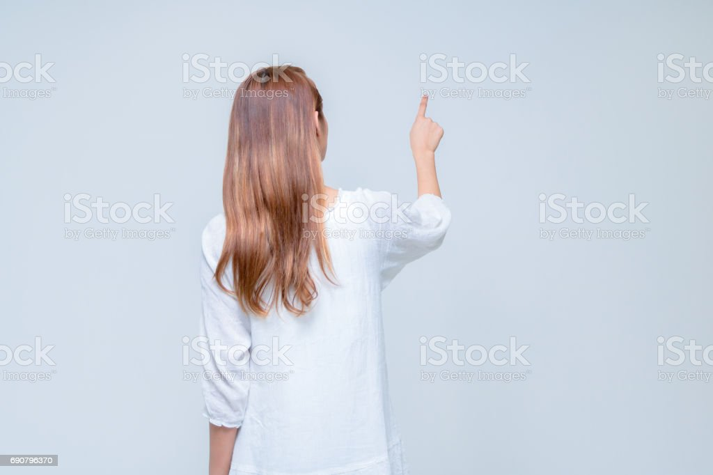 young latina girl pointing in the air stock photo
