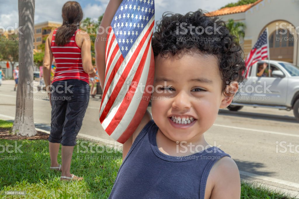 Young latina Mother with her happy boy at the parade. Fourth of July parade passes by as a Toddler boy holds the American flag up-looking at the camera with a-big smile. Adult Stock Photo