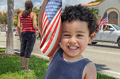 Fourth of July parade passes by as a Toddler boy holds the American flag up-looking at the camera with a-big smile.