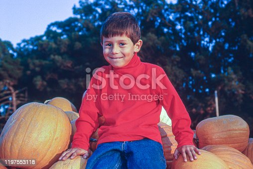 Young latino boy sitting on a pile of pumpkins that are ready for market.  Taken in Half Moon Bay, California, USA