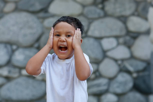 Young latino boy holding his head with both of his hands while laughing out loud expressing joy. stock photo