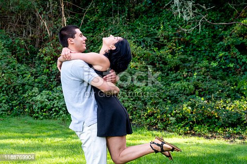Young Latino couple enjoying themselves in a wooded park.  Taken in Aptos, California, USA