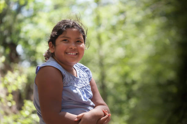 A young latino girl with a smile who is enjoying natures beauty, surrounded by trees with green foliage. stock photo