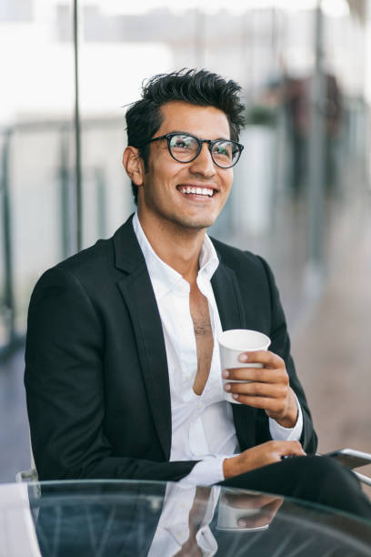Young latinx businessman having coffee break, smiling stock photo