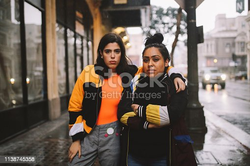 Vintage toned portrait of two young Latinx women, relaxing in downtown Los Angeles.
