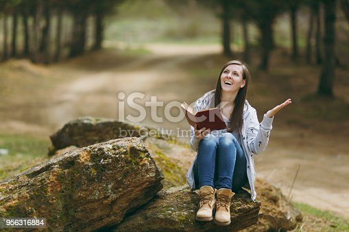 862602714istockphoto Young laughing beautiful woman sitting on stone studying reading book and spreading hands in city park or forest on green blurred background. Student learning, education. Lifestyle, leisure concept. 956316884