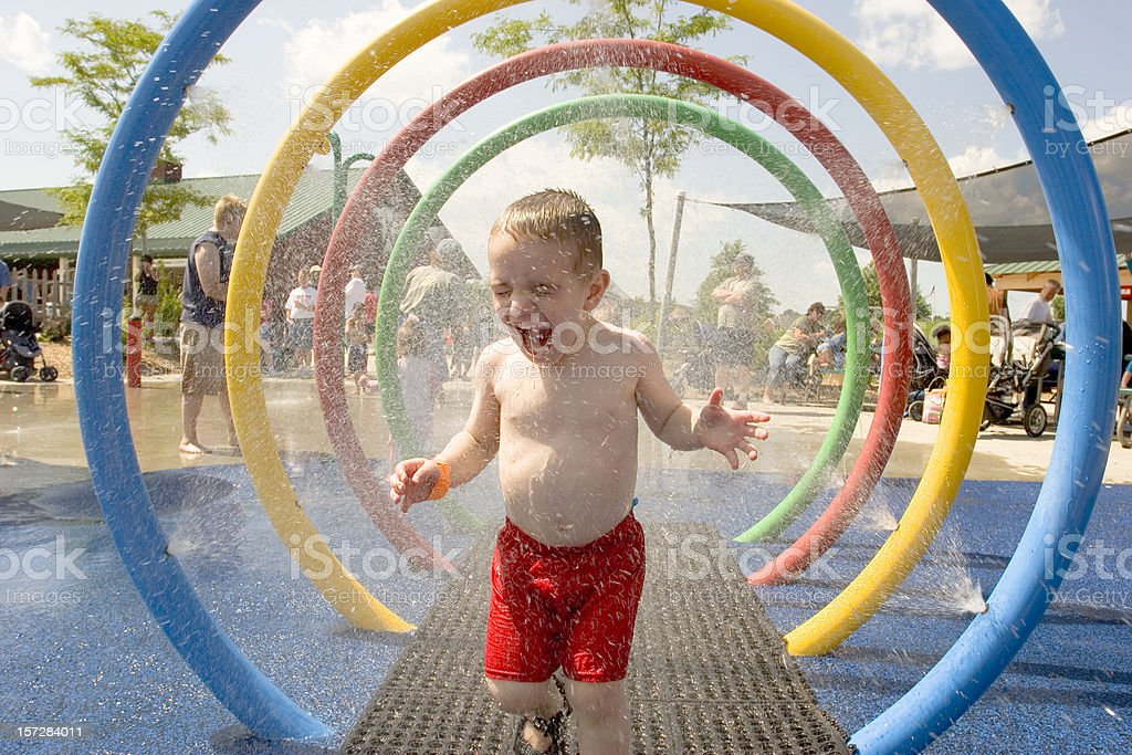 Young laughing boy runs through water park sprinklers stock photo