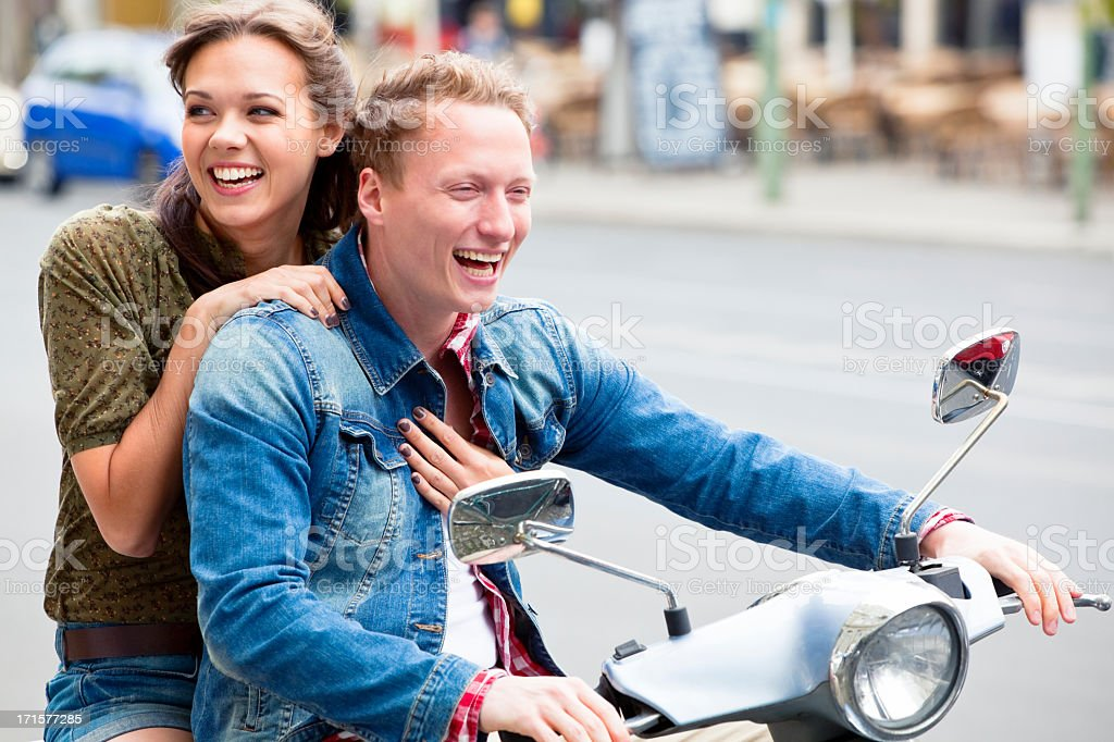 Young Laughing Couple Riding Scooter Throug the City stock photo
