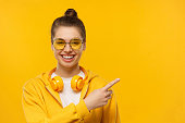 istock Young laughing girl wearing headphones around neck, pointing right, isolated on yellow background 1252905221