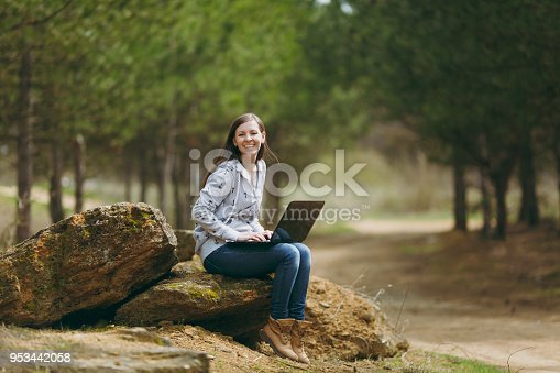 862602714istockphoto Young laughing successful smart business woman or student in casual clothes sitting on stone using laptop in city park or forest working outdoors on green blurred background. Mobile Office concept. 953442058
