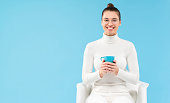istock Young laughing teenage girl in eyewear, holding cup of coffee in hands while sitting in white armchair, having rest from work, isolated on blue background 1252905104
