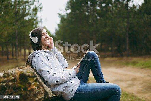 862602714istockphoto Young laughing woman in casual clothes sitting on stone listening music with headphones and tablet pc computer in city park or forest on green blurred background. Student lifestyle, leisure concept. 953441970