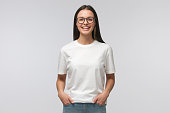 Young laughing woman standing with hands in pockets, wearing blank white t-shirt with copy space, isolated on gray background