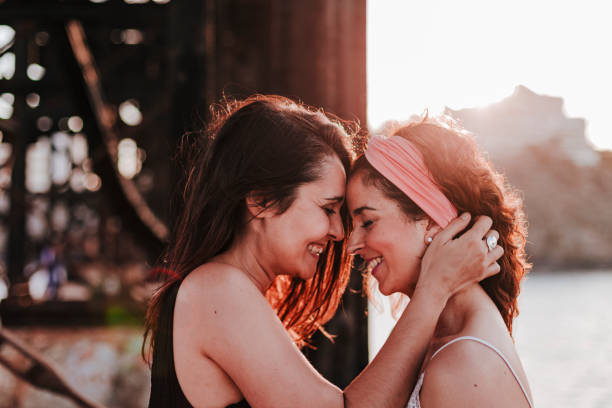 young lesbian couple hugging at sunset outdoors. Lifestyle and pride concept. love is love stock photo
