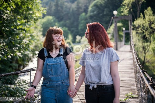 Two woman walking on the bridge and holding hands.