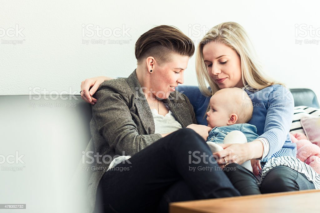 Young lesbian couple playing with baby on sofa stock photo