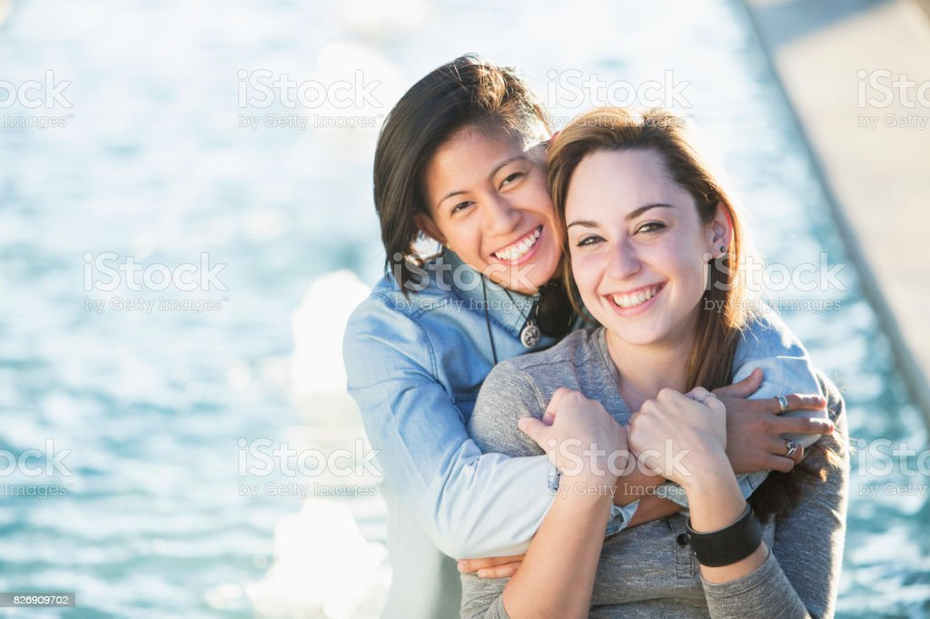 Young lesbian couple posing, in sunlight stock photo