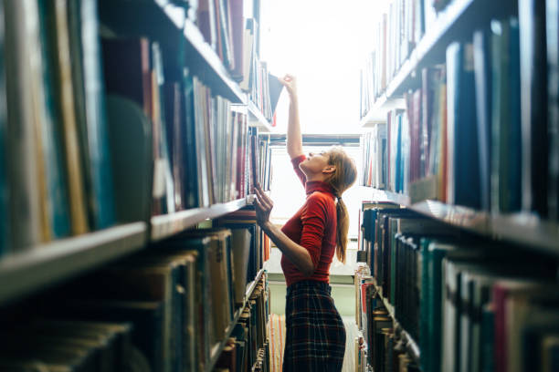 Young librarian picking book from bookshelf stock photo