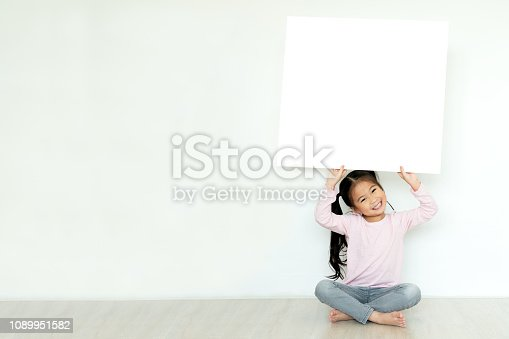 istock Young little asian girl or kid enjoy holding empty white placard board for media banner, business content presentation, mock up blank sign for message with positive and fun in creative design concept. 1089951582
