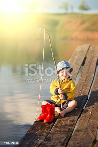 istock Young little boy fishing from wooden dock 925465634