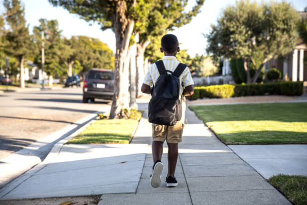 Young little boy walks to school in the morning stock photo
