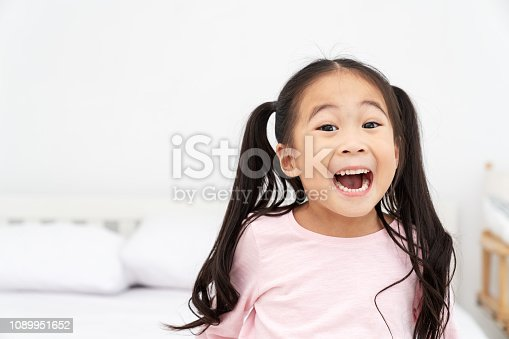 Young little cute asian girl smiling and laughing fun feeling excited, lucky and enjoy weeken in white room background with close up headshot view. Preschool asia kids or elementary children concept.