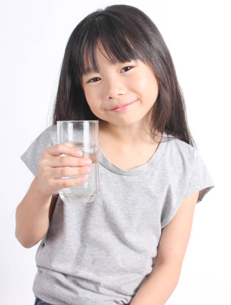2bcb044cc00 Young little girl drinking water stock photo