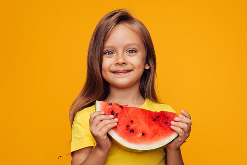 Young little girl eating watermelon