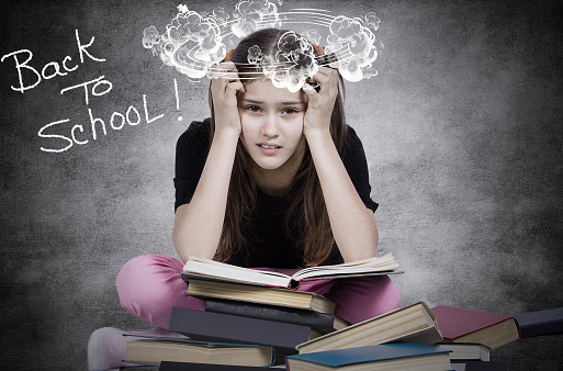 istock young little girl, stressed tired fatigued upset, sitting on pile of books, 671326730