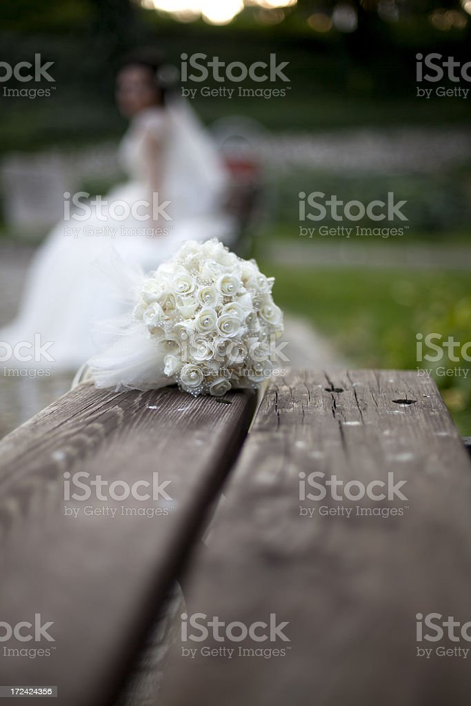 Young lonely bride with wedding dress standing in the park royalty-free stock photo