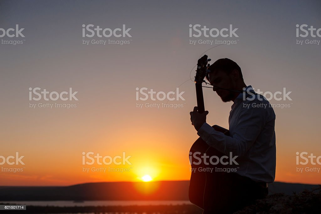 Young lonely guitarist playing on acoustic guitar photo libre de droits