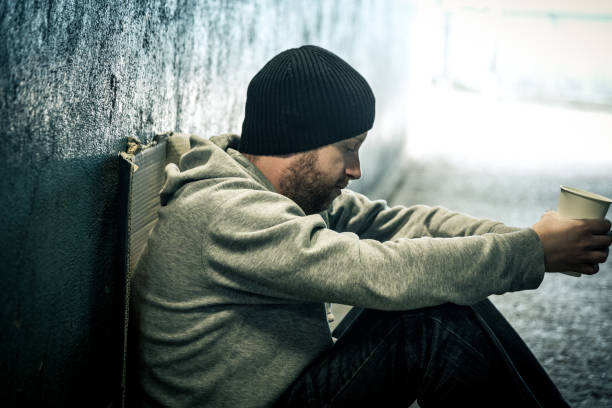 Young lonely homeless man sitting in dark subway tunnel stock photo