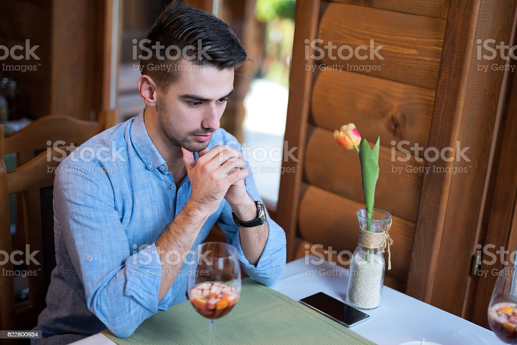 Young lonely man deep thinking in the restaurant stock photo