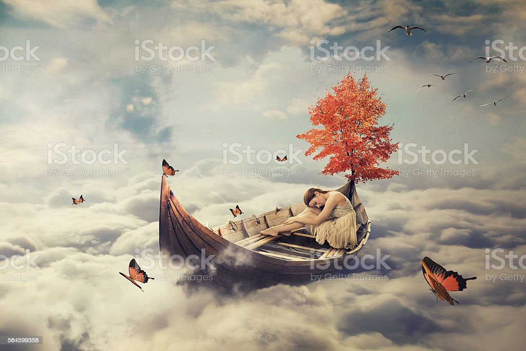 Young lonely woman drifting on boat above clouds. Dreamy screensaver stock photo