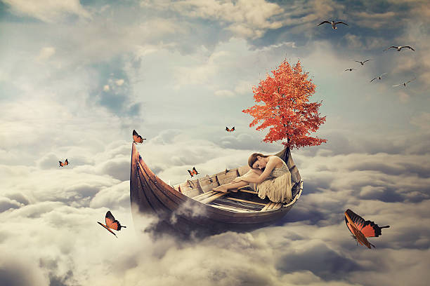 young lonely woman drifting on boat above clouds. dreamy screensaver - onirique photos et images de collection