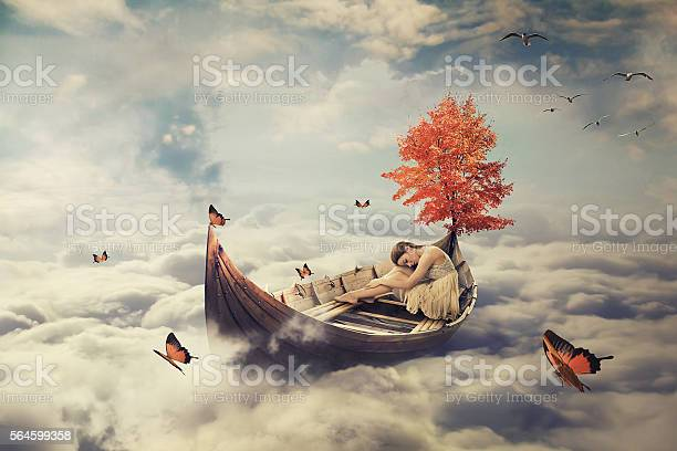 Photo of Young lonely woman drifting on boat above clouds. Dreamy screensaver