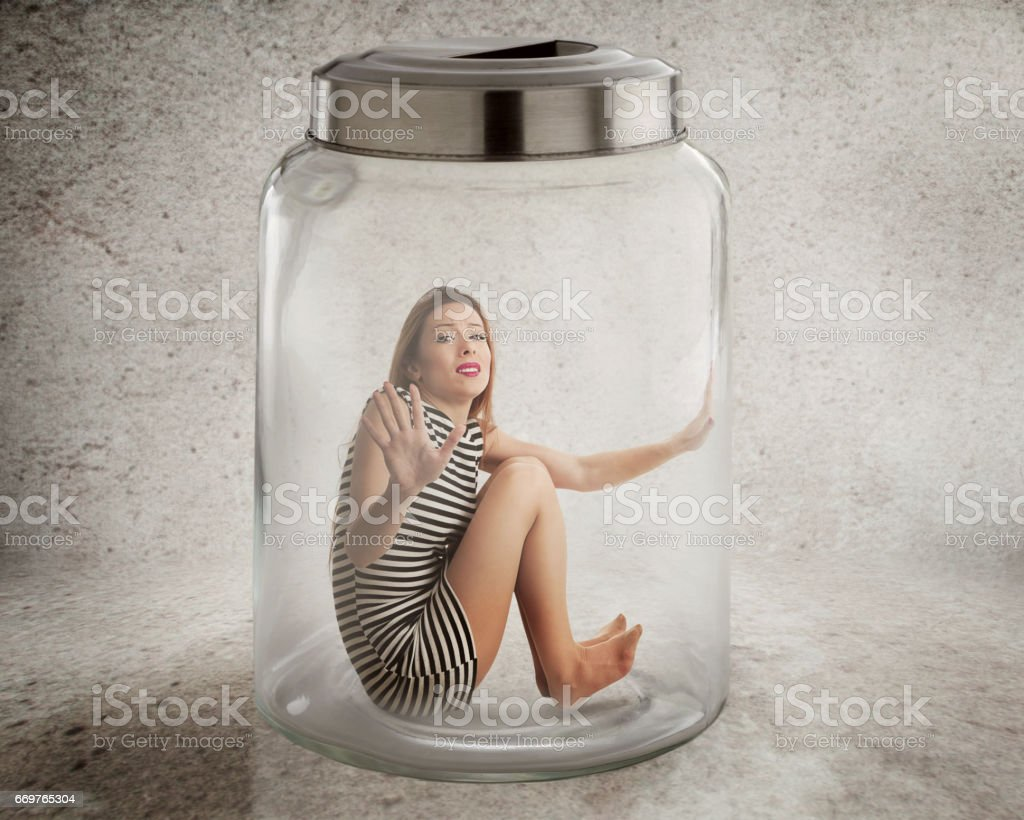 Young lonely woman sitting in glass jar isolated grey wall background stock photo