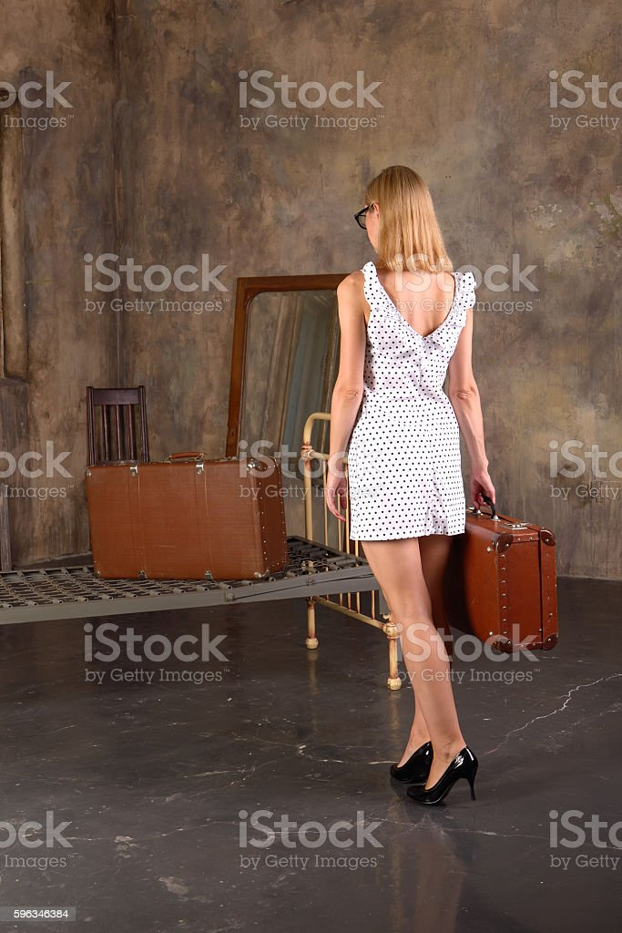 Young lonely woman with a suitcase enters the old apartment Lizenzfreies stock-foto