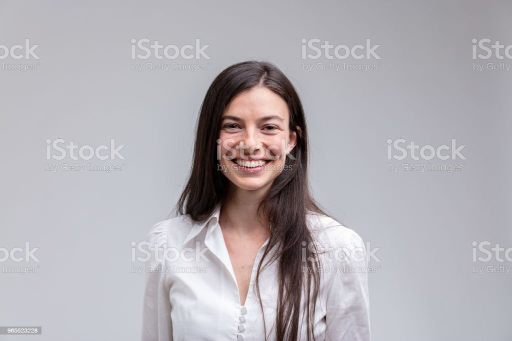 Young long-haired smiling woman in white shirt royalty-free stock photo