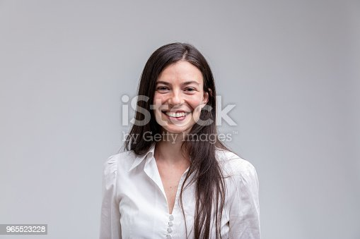 Portrait of young long-haired cheerful woman wearing white shirt against plain background