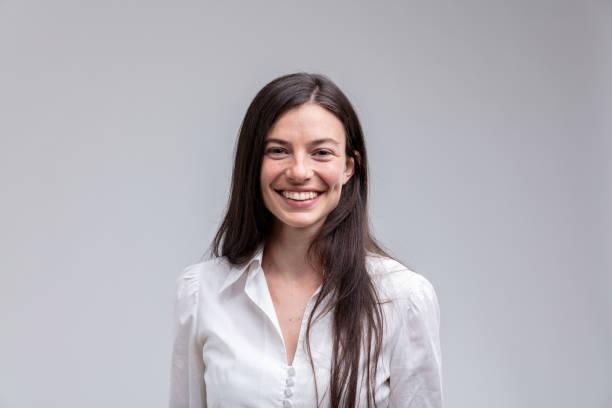 白色襯衣的年輕長髮微笑的婦女 - 年輕女性 個照片及圖片檔