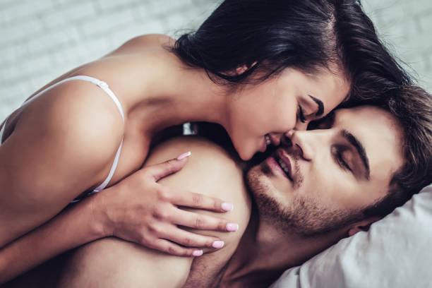 Amor do jovem casal na cama - foto de acervo