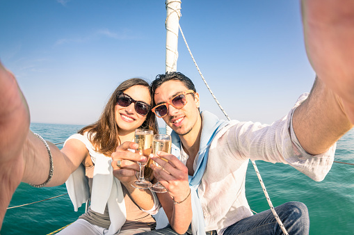 Young love couple taking selfie on sailing boat with champagne