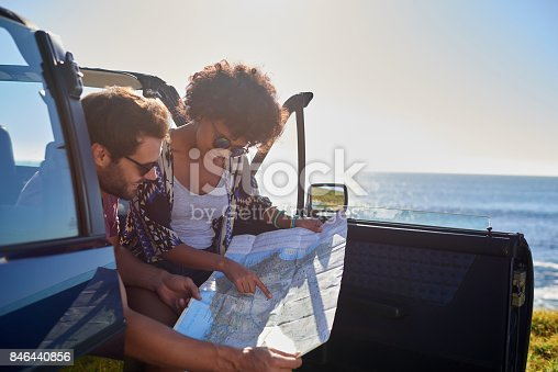 istock Young lovely couple using map during roadtrip 846440856
